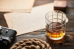 老测距仪照相机和威士忌酒与古色古香的地图 免版税库存图片