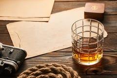 老测距仪照相机和威士忌酒与古色古香的地图 库存照片