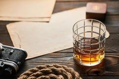 老测距仪照相机和威士忌酒与古色古香的地图 免版税库存照片