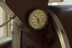 老温度计细节,安装在被放弃的咖啡烘烤器,电工业机器 免版税库存图片