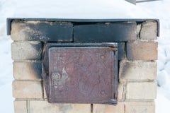 老火炉的门 一个老火炉在冬天 库存照片
