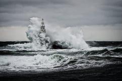 老灯塔在海在风暴日 免版税库存图片