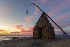 老灯塔由岩石做成,在美好的日出在Verdens Ende在西福尔郡挪威 免版税图库摄影