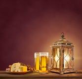 老灯笼用啤酒、乳酪和面包在葡萄酒背景 库存图片