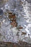 老灰色严重损坏了有深刻的安心和推出的红砖的混凝土墙,镇压和油漆和土各种各样的污点  库存照片