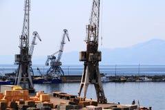 老灰色口岸起重机和小船,力耶卡,克罗地亚港口  免版税库存图片