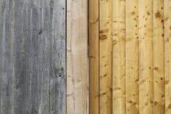 老灰色风化了篱芭板条和新的轻的金子褐色木头 库存照片