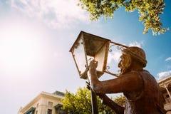 老点燃街灯的灯夫雕象,导致在第比利斯街道上的光  免版税库存图片