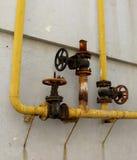 老煤气控制阀门和煤气管的系统在墙壁上 免版税图库摄影