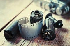 老照片胶卷、卡式磁带和减速火箭的照相机在背景 免版税库存照片