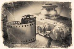 老照片胶卷和减速火箭的照相机在书桌上 图库摄影
