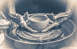 老照片葡萄酒 一个未加工的泥罐在陶瓷工的手上 免版税库存图片