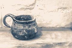 老照片葡萄酒 老黏土杯子站立木表面上 库存图片