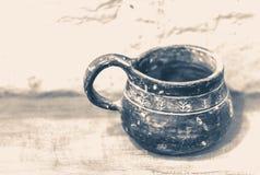 老照片葡萄酒 老黏土杯子站立木表面上 免版税库存照片