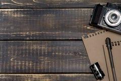 老照相机、一个笔记薄笔记的和一部影片在黑暗的木后面 免版税图库摄影