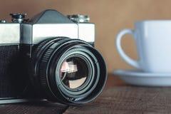老照相机和白色杯 图库摄影