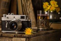 老照相机和黄色蒲公英 仍然生活葡萄酒 库存照片