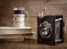 老照相机用在沿海航船和书的茶 库存图片