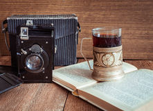 老照相机用在沿海航船和书的茶 免版税库存照片