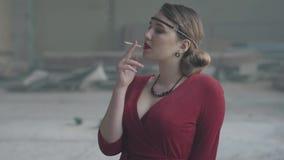 老牌布料火的画象确信的年轻女人sigaret 被放弃的被毁坏的大厦 影视素材