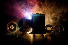 老牌放映机,特写镜头 在木背景的电影放映机与剧烈的照明设备和选择聚焦 电影和 库存照片