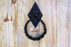 老牌金属雕刻了门把手和锁在米黄木背景 免版税库存照片