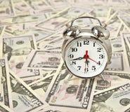 老牌闹钟和在美元背景 图库摄影