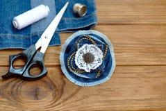 老牛仔裤的工艺想法 工艺品牛仔布花别针 剪刀,螺纹,顶针,针,在木背景的女性老牛仔裤 免版税库存图片