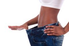 老牛仔裤的新非洲妇女在丢失的重量以后气喘 库存图片