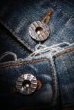 老牛仔裤和按钮 免版税库存照片