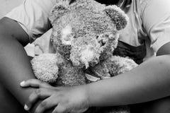 老玩具熊特写镜头与哀伤的男孩的 免版税库存照片