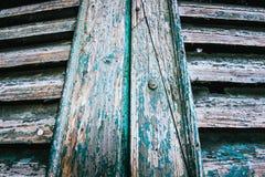 老生锈的削皮被绘的门快门 免版税库存图片