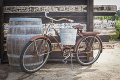 老生锈的古色古香的自行车和葡萄酒桶 免版税库存照片
