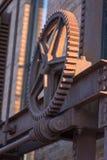 老生锈的工业钢齿轮和射线外面在阳光下 图库摄影