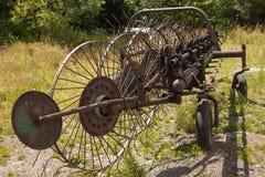 老生锈的干草特纳 在干草的老农业设备 免版税库存照片