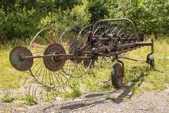 老生锈的干草特纳 在干草的老农业设备 免版税库存图片