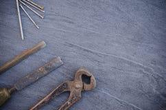 老生锈的手木匠业工具和钉子在一张木桌上 葡萄酒钳子 免版税库存照片