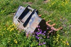 老生锈的挖掘机匙子在一个长得太大的野花草甸 库存图片