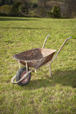 老生锈的独轮车推车在庭院里 库存照片
