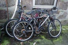 老生锈的自行车在花岗岩墙壁旁边停放了在阿伯丁市,苏格兰 库存图片