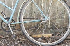 老生锈的自行车轮子在木篱芭附近的 免版税库存图片