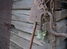 老生锈的金属链子、栅格、铁锹和灯笼在木lo 免版税库存图片