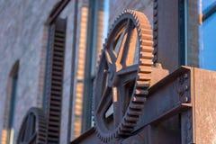 老生锈的钢齿轮砖工业仓库外 免版税图库摄影