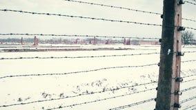老生锈的铁丝网篱芭和集中营遥远的被破坏的营房在雪的 4K steadicam射击 免版税库存图片