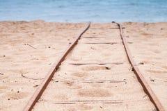 老生锈的铁路去在沙滩海 免版税库存照片