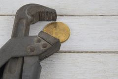 老生锈的银色管子扳手夹紧一金黄硬币bitcoin 库存照片