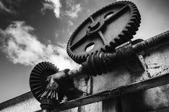 老生锈的齿轮在剧烈的天空下 库存照片