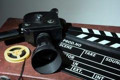 老电影摄影机拍板和卷轴与影片 库存图片
