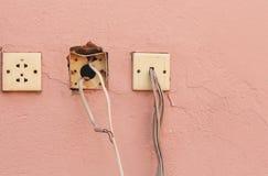 老电插口和导线在水泥墙壁上有拷贝空间的文本和设计书刊上的图片的 免版税图库摄影