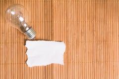 老电灯泡和空白的纸在木的 图库摄影